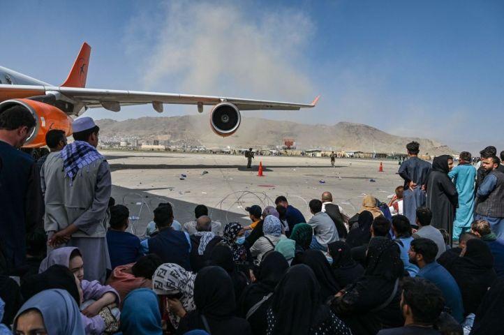 2021年8月16日、カブールの空港で出国を待つアフガニスタンの人々が座っている。20年に及んだアフガニスタンの戦争が驚くべき速さで終結し、タリバンの支配から逃れようと、何千人もの人々が空港に押し寄せた。(Photo by WAKIL KOHSAR/AFP via Getty Images)