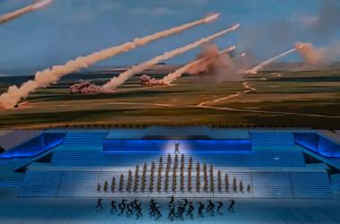 2021年6月28日、中国・北京国家体育場で開催された中国共産党結党100周年記念のイベントで、ロケットが発射される様子を映したスクリーンの前で、軍人に扮したパフォーマーがパフォーマンスを披露している。(Photo by Kevin Frayer/Getty Images)