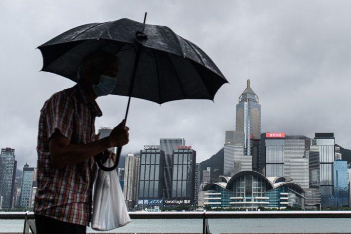 香港のビクトリア・ハーバーと香港島のスカイライン (後ろ) に面した九龍の尖沙咀(チムサーチョイ)海辺で傘を差す男性=2020年8月19日(Anthony Wallace/AFP via Getty Images)