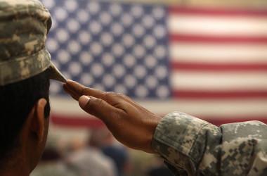 2011年6月、アフガニスタンからコロラド州フォートカーソンに到着した部隊の帰国歓迎式典で、兵士が国旗に敬礼している。参考写真(Photo by John Moore/Getty Images)