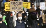 2021年3月13日、ワシントン州シアトルで行われた、アジア人に対するヘイトクライムに反対する集会で、「人種差別はウイルスだ(Racism is a Virus)」と書かれたサインを掲げる男性 (Jason Redmond/AFP via Getty Images)