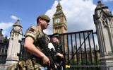 2017年5月24日、ロンドン中心部の国会議事堂付近で、武装警察官と一緒にパトロールする英国陸軍の兵士(JUSTIN TALLIS/AFP via Getty Images)