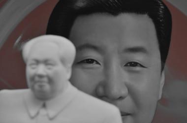 2018年2月27日、中国・北京の天安門広場の横にある土産物屋で、共産主義者の故・毛沢東の像の後ろに、中国の習近平総書記をイメージした飾り皿が見える。イメージ写真(GREG BAKER/AFP via Getty Images)