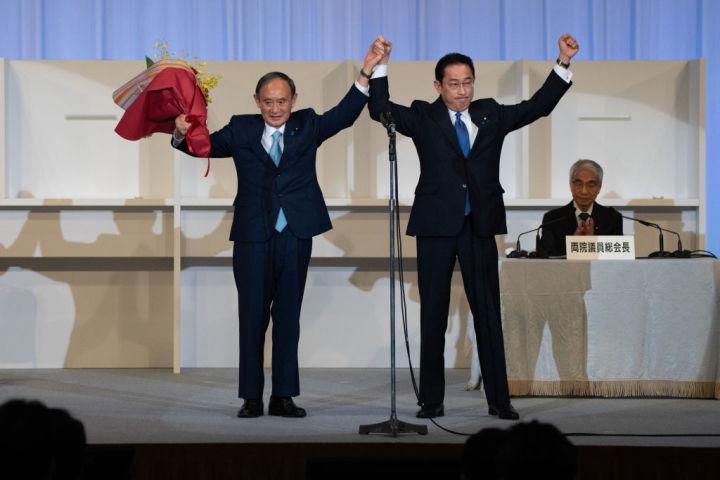 自民党総裁選後、手を取り合う菅義偉前総裁と岸田文雄新総裁 (Photo by Carl Court/Getty Images)