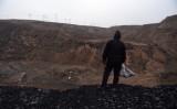 中国北部の山西省にある大同の炭鉱の近くで、石炭の山の上に立つ女性(GREG BAKER/AFP via Getty Images)