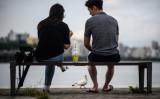 ソウルのハン川のほとりのベンチに座る男女、2021年7月撮影(Photo credit should read ED JONES/AFP via Getty Images)