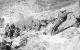 1950年12月6日、朝鮮戦争中の雪山での戦闘で、大きな岩の陰に身を隠しながら射撃するアメリカ海兵隊の歩兵たち(Hulton Archive/Getty Images)