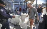 2019年10月2日、カリフォルニア州のサン・イシドロ入港地で、歩行者の書類をチェックする移民税関捜査局(ICE)の捜査官 (SANDY HUFFAKER/AFP via Getty Images)