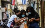 7月、キューバのハバナで携帯電話を見る若い女性たち。反政府デモが収束した頃インターネットの規制が緩和された(Photo by YAMIL LAGE/AFP via Getty Images)