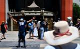 8月5日、米カリフォルニア州ロサンゼルスで、ハリウッドのTCLチャイニーズ・シアターの外でフェイスマスクを着用して記念撮影する観光客たち(Photo by PATRICK T. FALLON/AFP via Getty Images)